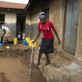 Slivia tries to negotiate steps outside her home in Uganda.